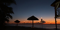 Colorful twilight on palm trees and thatched roof parasol silhouettes, with romantic fire torches on the beach, Cozumel Island Caribbean Sea, Mexico