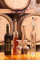 Oak barrels stacked in the wine cellar. Bottles on a table and glasses. One bottle marked with Dingac. Matusko Winery. Potmje village, Dingac wine region, Peljesac peninsula. Matusko Winery. Dingac village and region. Peljesac peninsula. Dalmatian Coast, Croatia, Europe.