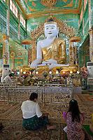 Myanmar, Burma.  Buddha Statue and Worshipers, near Mandalay.  Soon U Ponya Shin Pagoda, Sagaing Hill.