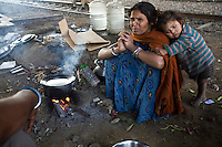 Aarti cooks breakfast on a piece of waste ground beneath a flyover near Okhla station.