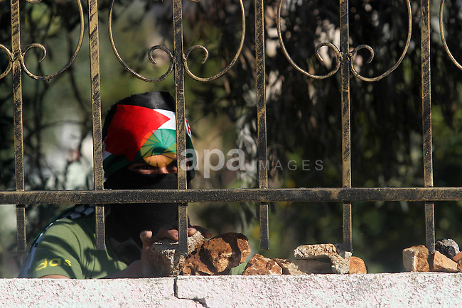 A Palestinian protester prepares stones during clashes with Israeli security forces in the West Bank village of Silwad, north of Ramallah, on March 21, 2014 following a protest of Palestinians against the expansion of the nearby Israeli settlement of Ofra. Photo by Issam Rimawi