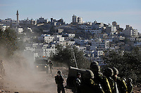 Israeli soldiers gather to organise a response as Jewish settler youths riot on the rooftop of a Palestinian house. Violence erupted as the Israeli army evicted a group of settlers from a disputed building in Hebron. The Israeli high court had rejected the settlers' claim that they legally bought the house from its Palestinian owner. As the house became a symbol of defiance, the few families living there were joined by a mob of some 1,500 radical right-wing youths, who went on a rampage and attacked Palestinians in the mixed West Bank city.