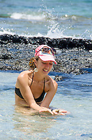 A local woman displays her find in a tide pool at a beach in Puako, South Kohala, Big Island.