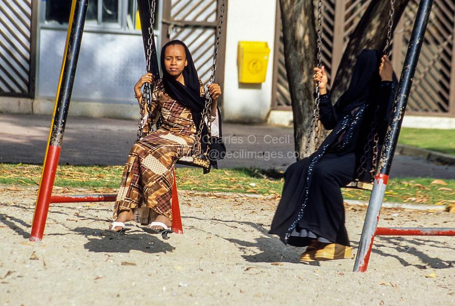 Mutrah, Oman.  Teenage Girls Swinging in Playground.