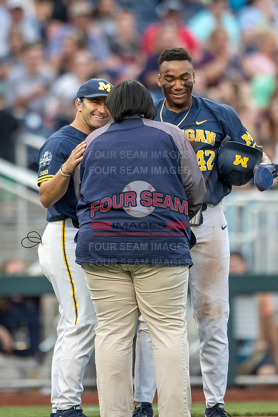 Michigan Wolverines designated hitter Jordan Nwogu (42) talks with team trainer Kimberly Hill and head coach Erik Bakich (23) after sliding head first into third base during Game 6 of the NCAA College World Series against the Florida State Seminoles on June 17, 2019 at TD Ameritrade Park in Omaha, Nebraska. Michigan defeated Florida State 2-0. (Andrew Woolley/Four Seam Images)