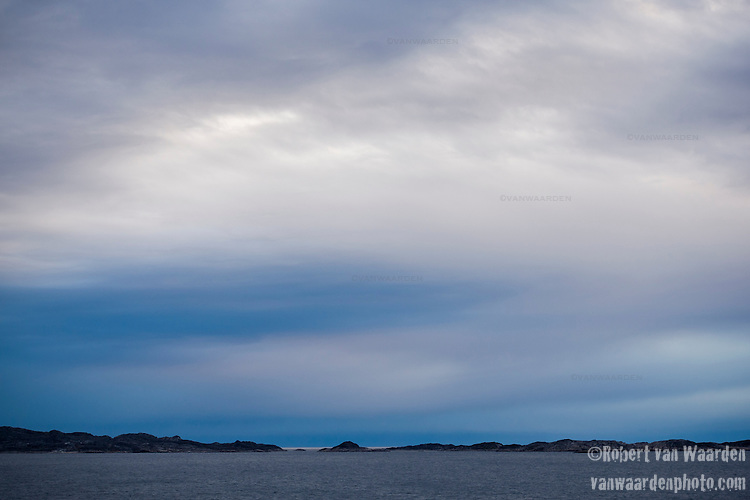 Blue and purple clouds and the landscape of Greenland's South coast.