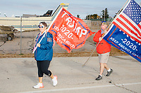 Two Trump supporters carry flags outside the Make America Great Again Victory Rally in the final week before the Nov. 3 election at Pro Star Aviation in Londonderry, New Hampshire, on Sun., Oct. 25, 2020.