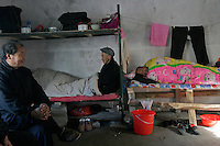This group of migrant carpenters chat, smoke or sleep in their dormitory when there is no work for them in a construction site in Beijing, China. They have basically no entertainment at all because they won't earn anything when there is no work..11 Mar 2006