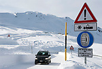 Italien, Suedtirol (Alto Adige), Pkw auf dem Jaufenpass (bei 2.000 m) im Winter, Hinweiszeichen fuer Schneeketten, Winterausruestung, Schneeraeumung | Italy, Alto Adige (South Tyrol), pass road Monte Giovo, sign for snow chains, car