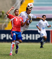 John Ruiz (9) of Costa Rica has the ball cleared away from him by Victorino Zelaya (3) of El Salvador during the group stage of the CONCACAF Men's Under 17 Championship at Jarrett Park in Montego Bay, Jamaica. Costa Rica defeated El Salvador, 3-2.