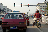 Taxis and motorcycles stopped at red traffic light, Datong, Shanxi, China.