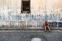 A Salvadoran sex worker sits on the curb while waiting for clients in the street in San Salvador, El Salvador, 10 November 2016. Although prostitution is not legal in El Salvador, dozens of street sex workers, wearing provocative miniskirts, hang out in the dirty streets close to the capital's historic center. Sex workers of all ages are seen on the streets but a significant part of them are single mothers abandoned by their male partners. Due to the absence of state social programs, they often seek solutions to their economic problems in sex work. The environment of street sex business is strongly competitive and dangerous, closely tied to the criminal networks (street gangs) that demand extortion payments. Therefore, sex workers employ any tool at their disposal to struggle hard, either with their fellow workers, with violent clients or with gang members who operate in the harsh world of street prostitution.