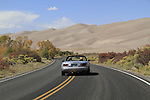 Silver sports car on highway leading into Great Sand Dunes National Park, Colorado. John offers private photo trips to Great Sand Dunes National Park and all of Colorado. All year long.