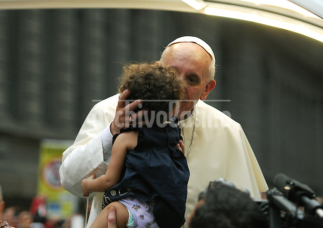 A member of the security detail holds up a baby to Pope Francis as he makes his way in the popemobile from Cathedral to downtown of Rio de Janeiro, Brazil, July 22, 2013. The pontiff arrived for a seven-day visit in Brazil and to participate at church's World Youth Day festival meeting legions of young Roman Catholics. (Austral Foto/Carlos Junior)
