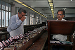 A tea tester tests the tea while his assistant take notes about the quality at the tea testing room of  J. Thomas ltd. company in Kolkata, West Bengal, India. Arindam Mukherjee