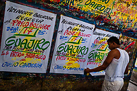 "A Colombian sign painter takes down just-finished music party posters in the sign painting workshop in Cartagena, Colombia, 12 December 2017. Hidden in the dark, narrow alleys of Bazurto market, a group of dozen young men gathered around José Corredor (""Runner""), the master painter, produce every day hundreds of hand-painted posters. Although the vast majority of the production is designed for a cheap visual promotion of popular Champeta music parties, held every weekend around the city, Runner and his apprentices also create other graphic design artworks, based on brush lettering technique. Using simple brushes and bright paints, the artisanal workshop keeps the traditional sign painting art alive."