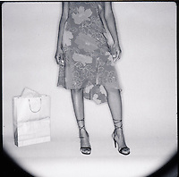 Lower torso of woman with shopping bag