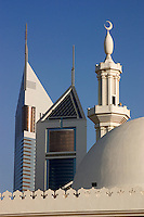 Dubai, United Arab Emirates. Emirates Towers with the dome and minarets of a mosque in the foreground. Sheikh Zayed Road, the Abu Dhabi Road,.