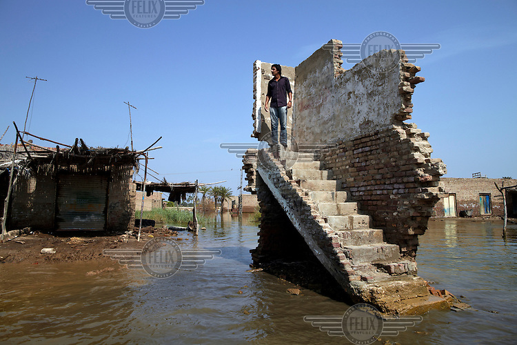 A man stands at the top of a destroyed building to gain a better view of the damage in Sultan Kot, Sindh Province, Pakistan.