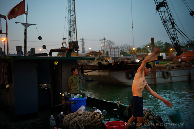 A men lifts a bucket into a boat docked along the Perfume river in Hue, Vietnam on 26 February 2010.