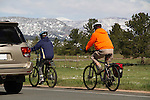 Couple riding bikes in traffic in Boulder, Colorado, USA. John leads private photo tours in Boulder, Denver and Rocky Mountain National Park, Year-round.