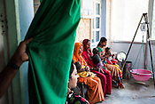 Caretakers wait to consult the health workers at the government health centre in  Hanuman Nagar, Saptari, Nepal.