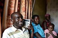 UGANDA, Arua, village Onduparaka, man and family listen radio
