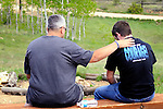 Two men sitting on a bench praying in the mountains