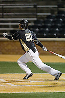 Justin Yurchak (20) of the Wake Forest Demon Deacons follows through on an RBI double against the Delaware Blue Hens at Wake Forest Baseball Park on February 13, 2015 in Winston-Salem, North Carolina.  The Demon Deacons defeated the Blue Hens 3-2.  (Brian Westerholt/Four Seam Images)