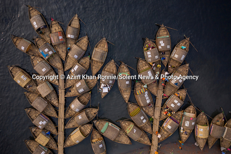 """Moored boats are arranged in such a way that it looks like they are branches of a tree. Photographer Azim Khan Ronnie managed to capture these moored boats, which were shaped in such a way that it reminded him of branches on a tree. The boats were moored on the Shitalakshya River in Narayanganj, Bangladesh and are used to carry passengers from one side of the river to the other. Azim said """"A boatman cannot carry passengers across the river whenever he wishes. They must maintain an order, controlled using ticket numbers.  After completing one trip across the river, the boat moves to the back of the queue and gets a new number. When his number is called up again, only then can he carry passengers across.""""<br /> <br /> Please byline: Azim Khan Ronnie/Solent News<br /> <br /> © Azim Khan Ronnie/Solent News & Photo Agency<br /> UK +44 (0) 2380 458800"""
