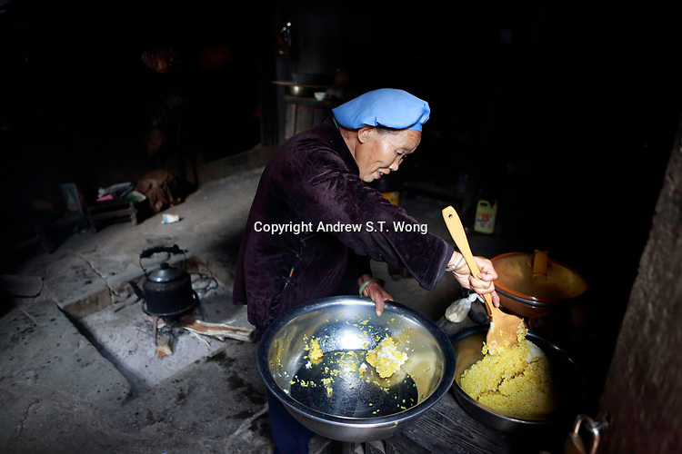 An elderly woman cooks traditional coloured sticky rice at Wangmo County in China's southwestern Guizhou Province, April 2019.