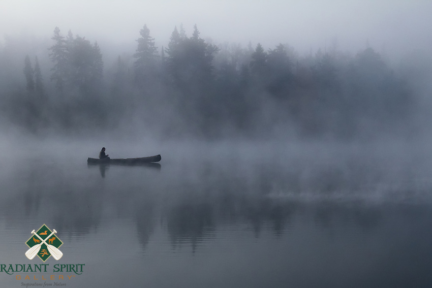 """""""Through the Fog""""<br /> <br /> The canoeist enjoys a foggy morning paddle in the Boundary Waters Canoe Area Wilderness (BWCAW). The silhouette of the canoeist effortlessly gliding along the river illustrates the peace and serenity we relish in the Boundary Waters. Soon the morning sun burned through the fog, as if raising the curtain to expose the incredible shoreline.<br /> <br /> This photograph is from our Canoescapes Series. It was also a semi-finalist for the Wilderness Forever Exhibit at the Smithsonian National Museum of Natural History."""