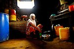 A woman washing dishes in her kitchen in Likoni, Kenya