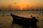 Boats and pelicans, Pelecanus,are silhouetted against the early morning sky in Los Roques, Venezuela.