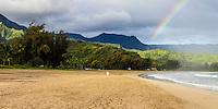 A woman enjoys the morning with a rainbow at Hanalei Beach and Hanalei Bay, Kaua'i.