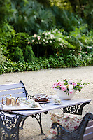 Afternoon tea is served al fresco on an outdoor table adorned with freshly cut roses