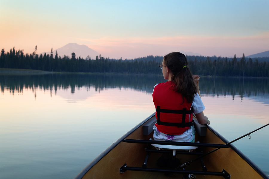 Girl paddling canoe on Hosmer Lake at dusk, Mountain Bachelor in background, Cascade Lakes, Oregon, USA