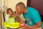 12 month old baby boy with father sitting in child seat fed solid food baby offering bite of snack food or cracker to father horizontal