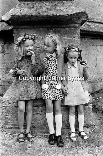 """Painswick Clypping Gloucestershire Uk Girls eating """"Clypping Buns""""."""