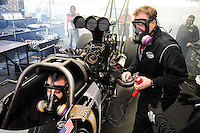 Feb. 12, 2012; Pomona, CA, USA; NHRA top fuel dragster driver Shawn Langdon (left) sits in the car as crew chief Brian Husen monitors the engine during the Winternationals at Auto Club Raceway at Pomona. Mandatory Credit: Mark J. Rebilas-