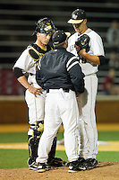 Wake Forest Demon Deacons pitching coach Dennis Healy has a chat on the mound with starting pitcher Justin Van Grouw #30 and catcher Brett Armour #6 during the game against the Florida State Seminoles at Wake Forest Baseball Park on March 24, 2012 in Winston-Salem, North Carolina.  The Seminoles defeated the Demon Deacons 3-2.  (Brian Westerholt/Four Seam Images)