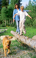 Mother and son playing by balancing on a log in the forrest