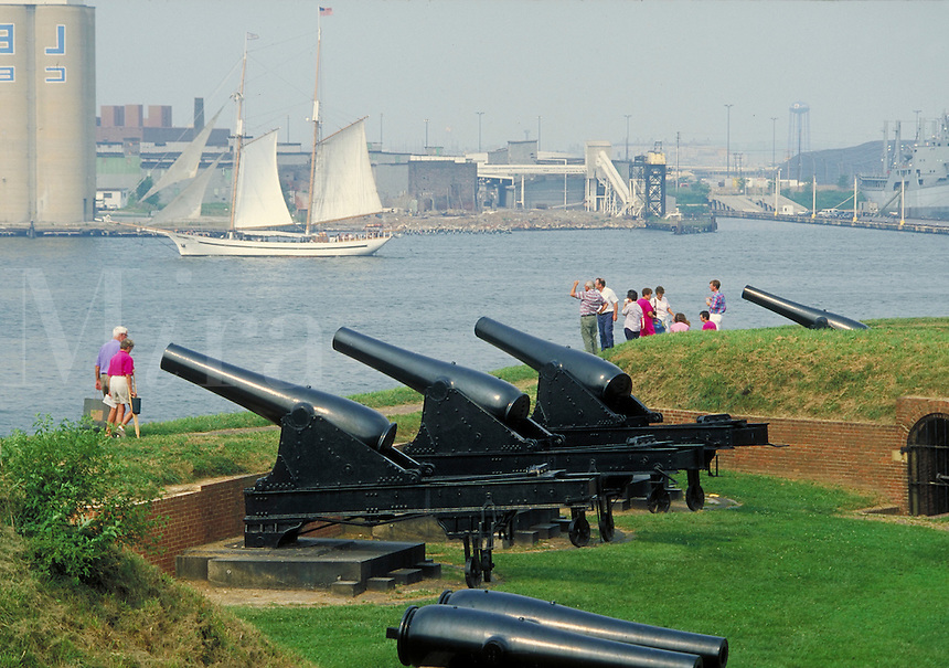 tourists viewing classic sailing ship with cannons in foreground at Fort McHenry National Monument. tourists. Baltimore Maryland USA.