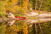 """""""Fall Landing""""<br /> Our canoes await their next outing on our Fall wilderness trip in the Boundary Waters Canoe Area Wilderness (BWCAW). As we explored our newly discovered campsite, I caught sight of our cherry red canoes along the autumn-kissed shoreline. The scene perfectly reflected the wilderness experience in autumn. <br /> <br /> This photograph is from our Canoescapes Series. It was also recognized as one of 10 finalists in the Sustainable Travel category of the 13th Annual Smithsonian Photo Contest. There were 46,000 entries from 168 countries."""