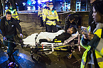 """© Joel Goodman - 07973 332324 . NO SYNDICATION PERMITTED . CAUTION RE ID OF MAN RECEIVING TREATMENT . 20/12/2014 . Manchester , UK . Paramedics carry a man with a head injury on to a trolley to an ambulance , outside Deansgate Locks nightclub venue . The ambulance took over 40 minutes to arrive . """" Mad Friday """" revellers out in the rain and cold in Manchester . Mad Friday is typically the busiest day of the year for emergency services , taking place on the last Friday before Christmas when office Christmas parties and Christmas revellers enjoy a night out .  Photo credit : Joel Goodman"""