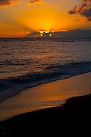 A brilliant sunset lighting up one of Kauai's beautiful south shore beaches near the town of Waimea.