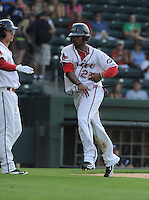 Left fielder Keury De la Cruz (25) of the Greenville Drive is congratulated after scoring a run in a game against the Rome Braves on July 6, 2012, at Fluor Field at the West End in Greenville, South Carolina. Greenville won, 4-0. (Tom Priddy/Four Seam Images)