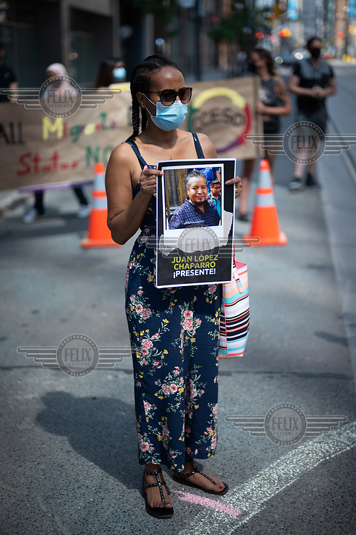 A woman holds picture of Juan Lopez Chaparro, a Mexican migrant worker who died from COVID-19, as the Migrant Workers Alliance for Change stages a demonstration where a human clock reads five minutes to midnight at the The Immigration and Refugee Board of Canada building, at 74 Victoria Street.