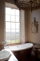 A strategically placed roll top bath affords views over the fields beyond the Capability Brown gardens