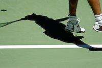 A shadow of a man playing tennis on the court.